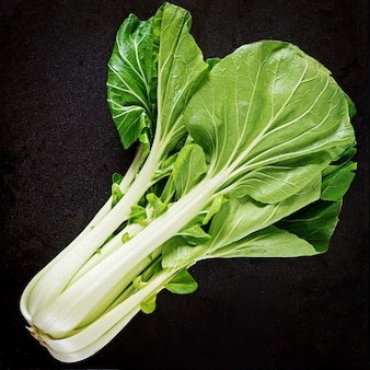 黒いテーブルの上のチンゲン菜または白菜。パクチョイ。上面図