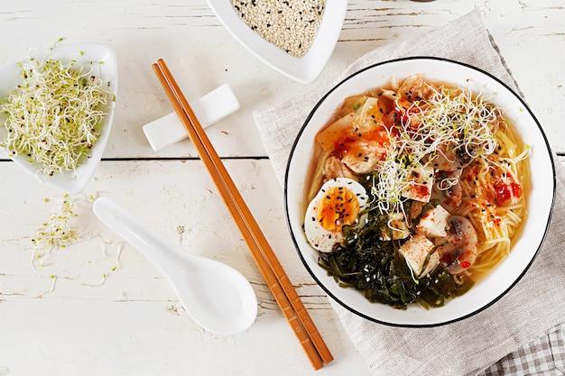 白い木製のテーブルの上にボウルにキャベツキムチ、海藻、卵、キノコ、チーズ豆腐の味噌ラーメンアジアンヌードル。韓国料理上面図。フラットレイ