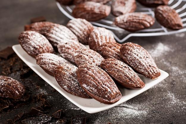 暗いテーブルの上の自家製チョコレートマドレーヌ