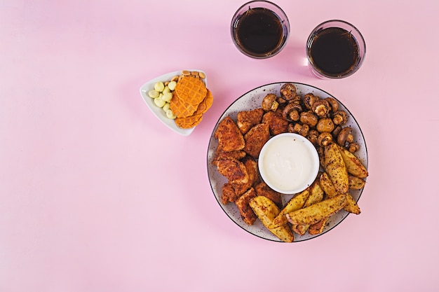 ケチャップ、フライドポテト、焼きマッシュルーム、コーラを添えたファーストフードチキンナゲット。