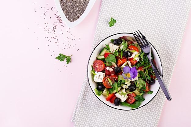 Греческий салат с огурцом, помидорами, сладким перцем, листьями салата, зеленым луком, сыром фета