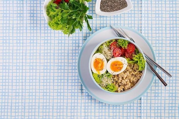 新鮮なサラダ。オートミール、トマト、レタス、マイクログリーン、ゆで卵の朝食ボウル。健康食品。