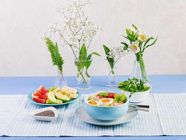 新鮮なサラダ。オートミール、トマト、レタス、マイクログリーン、ゆで卵の朝食ボウル。