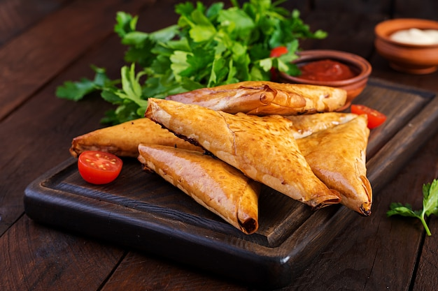 アジア料理。サムサ(サモサ)、鶏ムネ肉と木製のチーズ。