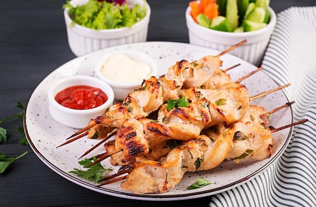 Куриный шашлык. шашлык - мясо на гриле и свежие овощи.