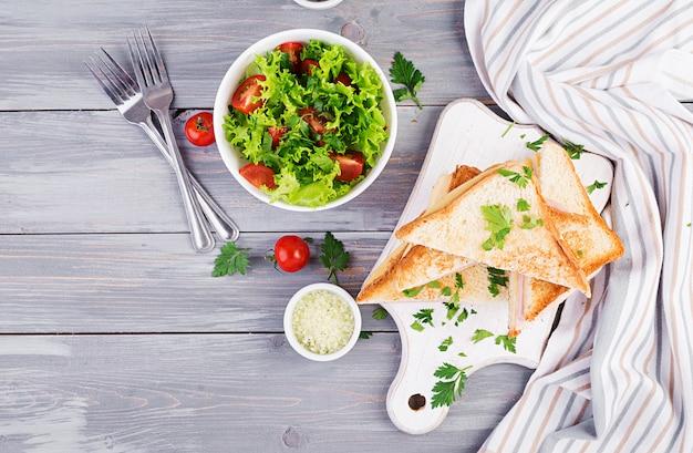 クラブサンドイッチパニーニ、ハム、チーズ、サラダ。上面図。おいしい朝食