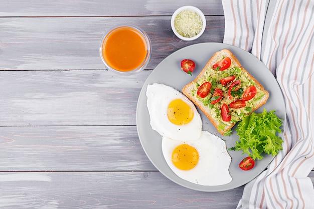 朝ごはん。目玉焼き、野菜サラダ、灰色の背景に焼きアボカドサンドイッチ。上面図