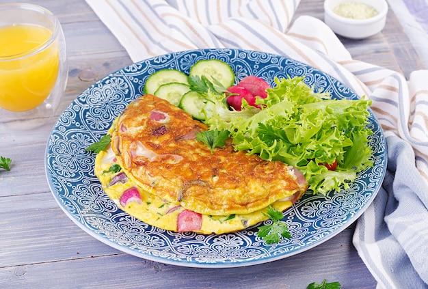 朝ごはん。大根、赤玉ねぎ、青皿に新鮮なサラダのオムレツ。フリッタータ-イタリアのオムレツ。