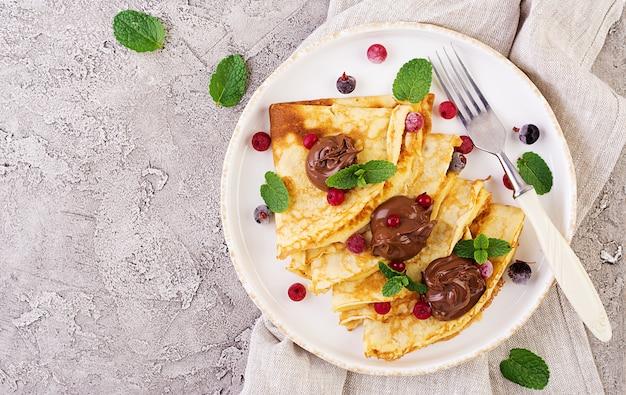 ミントの葉で飾られたベリーとチョコレートのパンケーキ。おいしい朝食。上面図