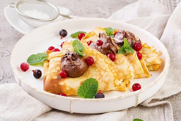 ミントの葉で飾られたベリーとチョコレートのパンケーキ。おいしい朝食。