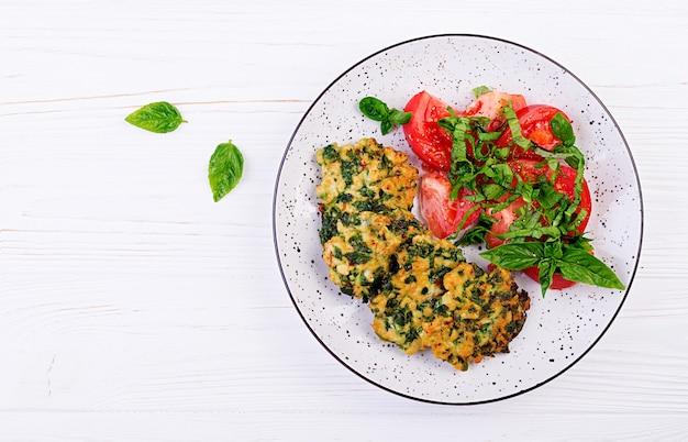ほうれん草とトマトのサラダのおかずと焼きステーキみじん切りチキンの切り身。ヨーロッパ料理。ダイエット食品。上面図
