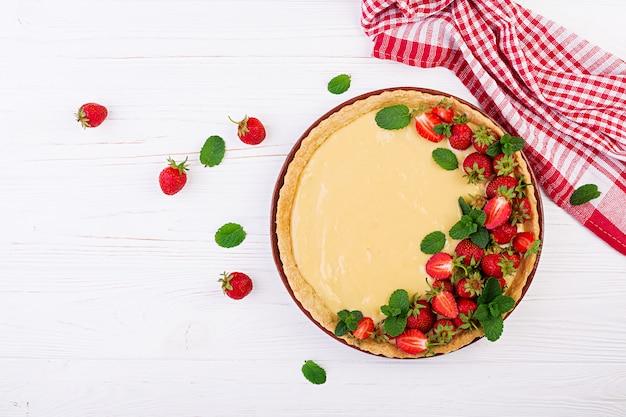 ミントの葉で飾られたイチゴとホイップクリームのタルト