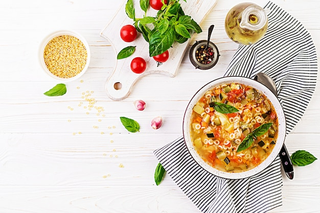 Минестроне, итальянский овощной суп с макаронами на белом столе
