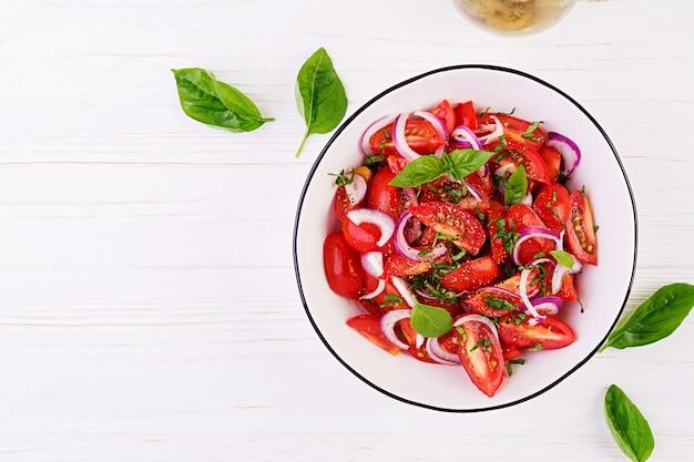 Салат из помидоров с базиликом и красным луком. концепция здорового питания. веганская кухня