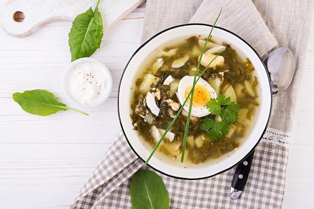 白いボウルにスイバの緑のスープ、フラットレイアウト、トップビュー