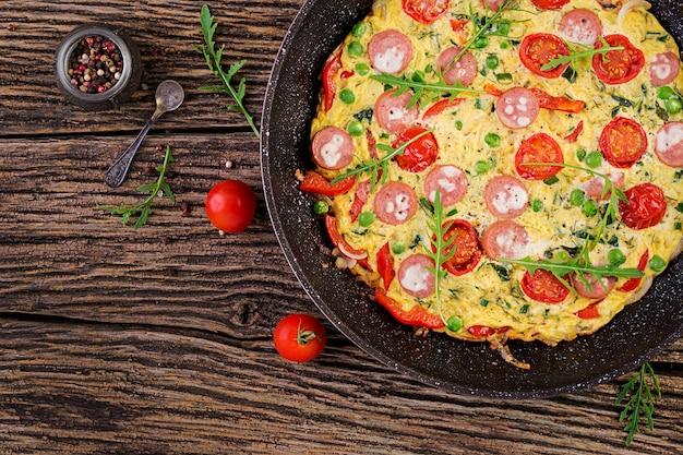 トマト、ソーセージ、素朴なスタイル、トップビューでグリーンピースのオムレツ