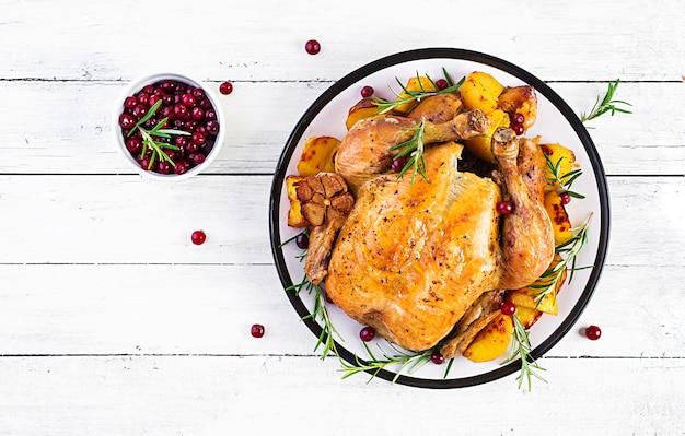 秋の紅葉を飾った素朴なスタイルのテーブルにクランベリーを添えた七面鳥のロースト。感謝祭。焼きチキン。上面図