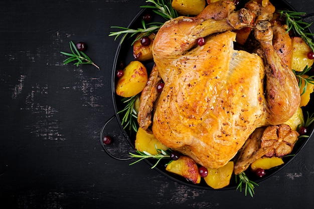 焼き七面鳥または鶏肉。クリスマステーブルには七面鳥が添えられ、明るい見掛け倒しで飾られています。フライドチキン。テーブルセッティング。クリスマスディナー。上面図