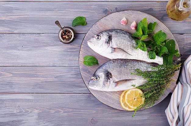 まな板で調理する緑のハーブと生のドラド魚。上面図