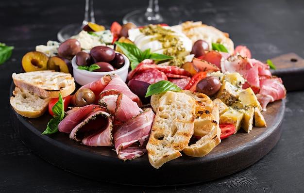 Антипасто с ветчиной, прошутто, салями, голубым сыром, моцареллой с соусом песто и оливками.