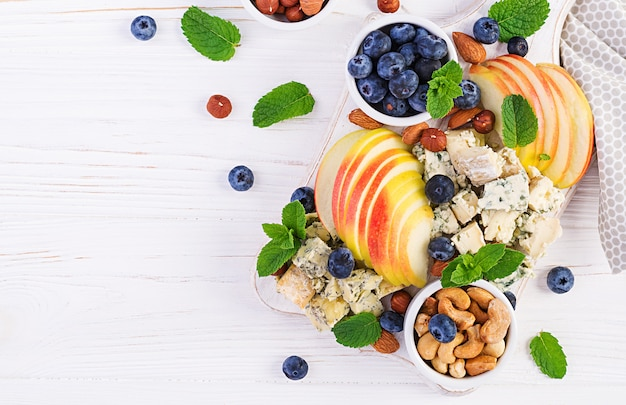 チーズ盛り合わせ、チーズの盛り合わせ、ブルーベリー、リンゴ、白いテーブル上のナッツ。イタリアのチーズの盛り合わせとフルーツ。上面図、オーバーヘッド