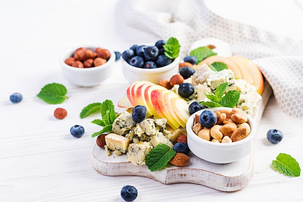 チーズ盛り合わせ、チーズの盛り合わせ、ブルーベリー、リンゴ、白いテーブル上のナッツ。イタリアのチーズの盛り合わせとフルーツ。