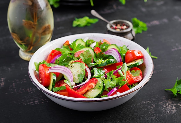 Салат из помидоров и огурцов с красным луком, паприкой, черным перцем и петрушкой. веганская еда. диетическое меню.