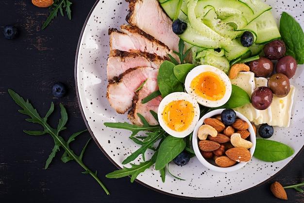 ケトジェニックダイエット。ケトブランチ。ゆで卵、豚肉ステーキ、オリーブ、キュウリ、ほうれん草、ブリーチーズ、ナッツ、ブルーベリー。上面図