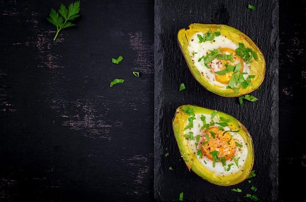 卵と新鮮なサラダで焼いたアボカド。ベジタリアン料理。平面図、オーバーヘッド。ケトジェニックダイエット。ケトフード