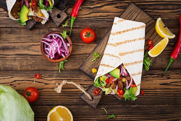 牛肉のトマトソースとアボカドサルサのメキシコのタコス。平干し。上面図