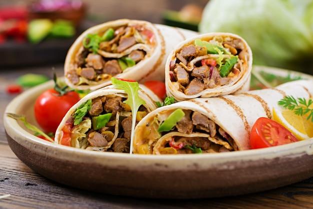 ブリトーは、牛肉と野菜を木材で包みます。ビーフブリトー、メキシコ料理。健康食品の背景。メキシコ料理。