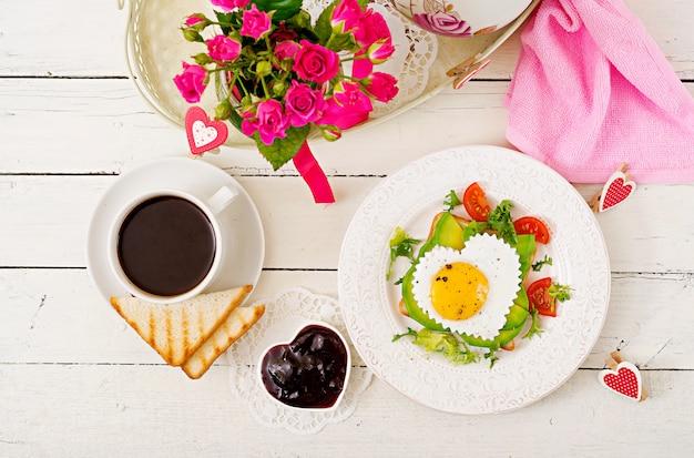 バレンタインデーの朝食-ハート、アボカド、新鮮な野菜の形をした目玉焼きのサンドイッチ。一杯のコーヒー。イングリッシュブレックファースト。上面図
