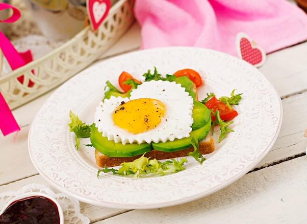 バレンタインデーの朝食-ハート、アボカド、新鮮な野菜の形をした目玉焼きのサンドイッチ。一杯のコーヒー。イングリッシュブレックファースト。