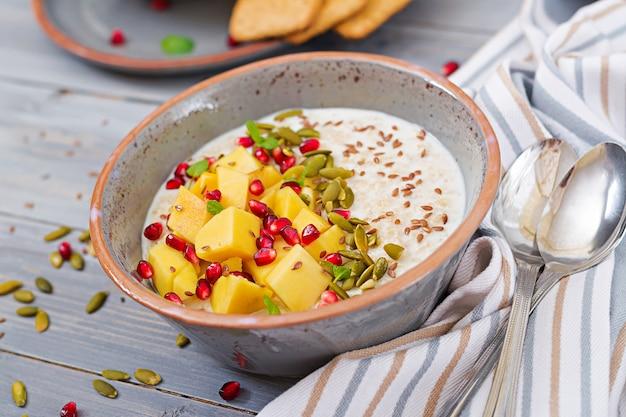 マンゴー、ザクロ、種子入りのおいしいヘルシーなオートミールポリッジ。健康的な朝食。フィットネス食品。適切な栄養。