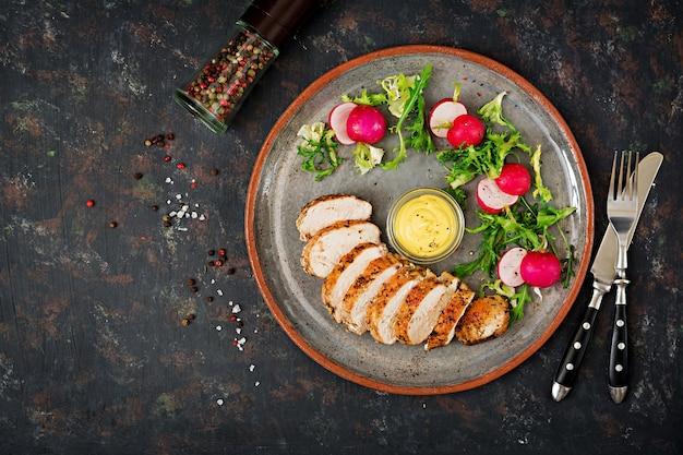 焼きたての鶏の胸肉と新鮮な野菜を暗いプレートに乗せます。食事メニュー。平干し。上面図