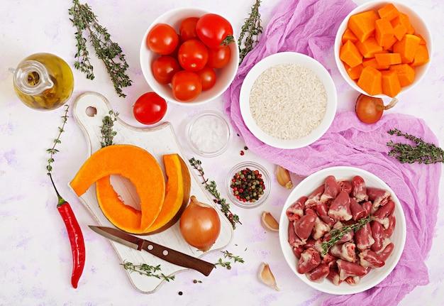 Ингредиенты для приготовления куриных сердечек с тыквой и помидорами в томатном соусе. гарнир подается с отварным рисом. квартира лежала. вид сверху.