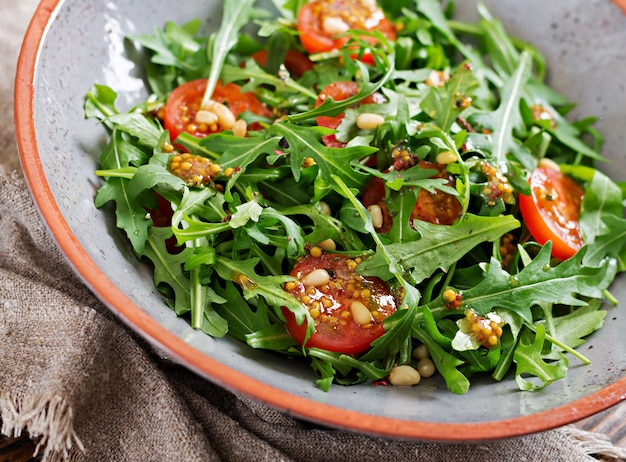 食事メニュー。ビーガン料理。ルッコラ、トマト、松の実のヘルシーサラダ。