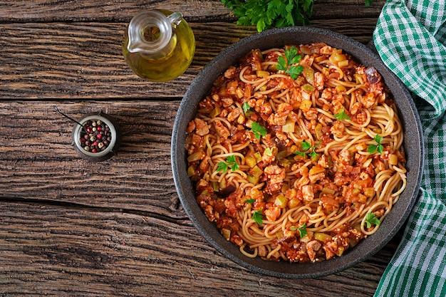 Макароны спагетти болоньезе с томатным соусом, овощами и фаршем - домашние здоровые итальянские макароны на деревенском стиле деревянных фоне. вид сверху. плоская планировка