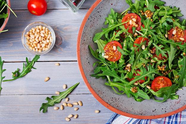 食事メニュー。ビーガン料理。ルッコラ、トマト、松の実のヘルシーサラダ。平干し。上面図