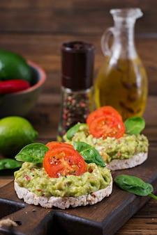 健康的な朝食。ワカモレと木製の背景にトマトのサンドイッチのぱりっとしたパン。