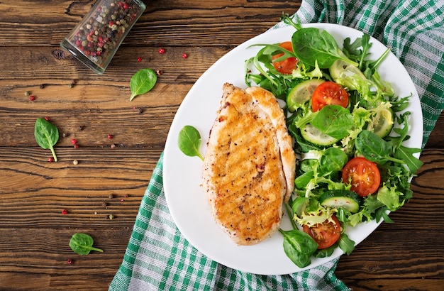 鶏胸肉のグリルと新鮮野菜のサラダ-トマト、キュウリ、レタスの葉。チキンサラダ。健康食品。平干し。上面図