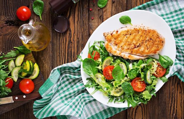 Жареная куриная грудка и салат из свежих овощей - помидоры, огурцы и листья салата. салат с курицей. здоровая пища. квартира лежала. вид сверху