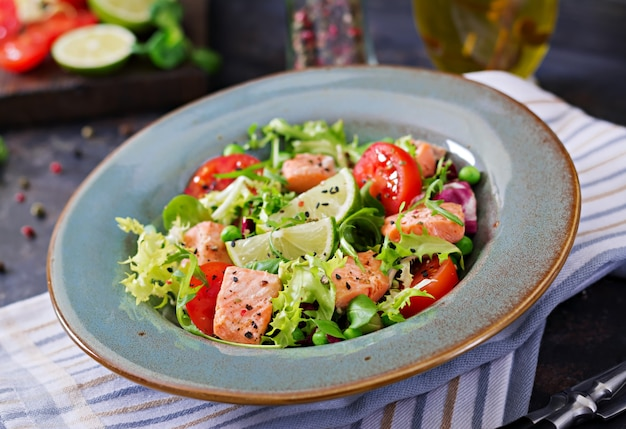 Полезный салат с рыбой. запеченный лосось, помидоры, лайм и салат. здоровый ужин.