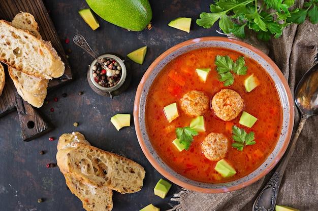 ミートボールと野菜のスパイシートマトスープ。アボカドとパセリを添えて。健康的な夕食。上面図