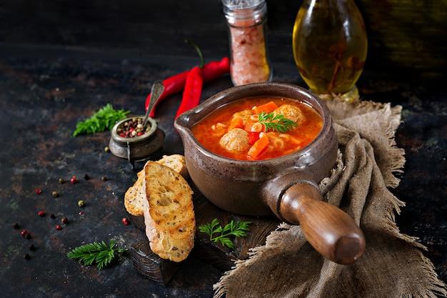 ミートボール、パスタ、野菜のピリ辛トマトスープ。健康的な夕食