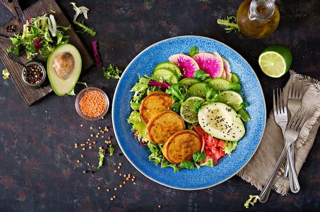 ビーガンブッダボウルディナーフードテーブル。健康食品。健康的なビーガンランチボウル。レンズ豆と大根のアボカドサラダのフリッター。平干し。上面図