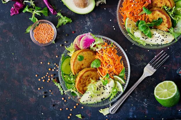 ビーガンブッダボウルディナーフードテーブル。健康食品。健康的なビーガンランチボウル。レンズ豆と大根、アボカド、ニンジンのサラダのフリッター。平干し。上面図