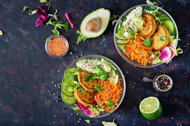 Веганские будды чаши обеденный стол. здоровая пища. здоровый веганский ланч. оладьи с чечевицей и редькой, авокадо, салат из моркови. квартира лежала. вид сверху