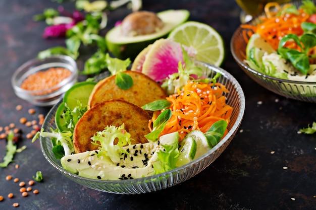 Веганские будды чаши обеденный стол. здоровая пища. здоровый веганский ланч. оладьи с чечевицей и редькой, авокадо, салат из моркови.