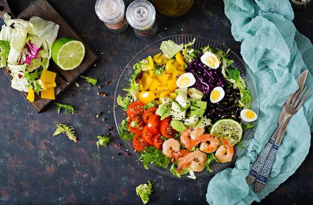 ヘルシーなサラダプレート。新鮮なシーフードのレシピ。エビのグリルと新鮮野菜のサラダ-アボカド、トマト、黒豆、赤キャベツ、パプリカ。海老のグリル。